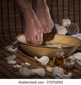 Female feet with drops of water, spa bowl, towels, flowers, candles, sea salt and bottle with essential oil. Foot spa concept.