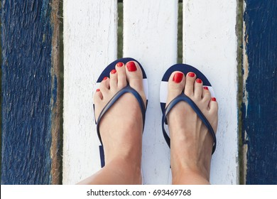 Female feet with flip flops on the jetty. Top view