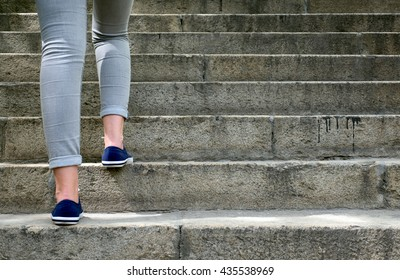 Female feet in gym shoes to climb the stairs in the daytime