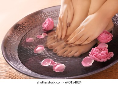 Female feet and hands with brown manicure in bowl with flowers at spa salon, closeup