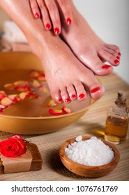 Female feet and hands with spa bowl, flowers, sea salt and bar soap on wooden background. Foot spa concept.