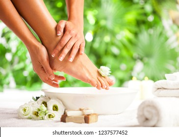 Female feet and hands with spa bowl, towel, soap and flowers on white floor and tropical green leaves background
