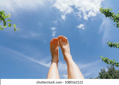 Female feet up infront of the cloudy sky