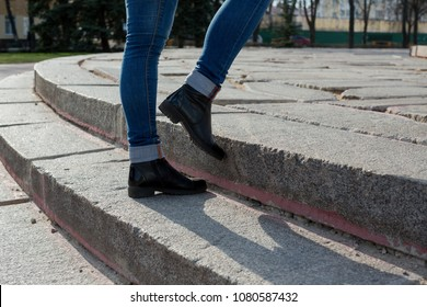 Female feet in jeans and black boots stumble up the granite ladder