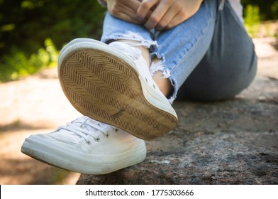 Female feet in jeans and sports shoes.