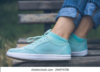 Female feet in jeans and sports shoes. Sneakers are on a wooden bench in a park close-up. Woman resting on the bench after the walk.