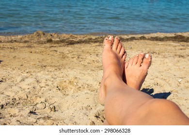Female feet on blue sea background. Woman sunbathes on beach. Girl taken pictures of her self.