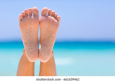 Female feet on blue sky and sea background