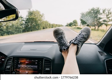 Female feet on a car dashboard by the windshield. Road trip concept.