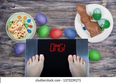 Female feet on digital scales with sign omg! surrounded by Easter food (Easter cake, chocolate Easter bunny, painted eggs). Consequences of overeating and unhealthy lifestile during holidays. Top view