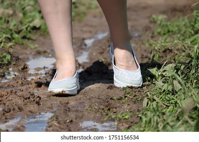 Female feet on a muddy path, shoes soiled in mud. Rural street with puddles after rain in summer, woman walking in the countryside