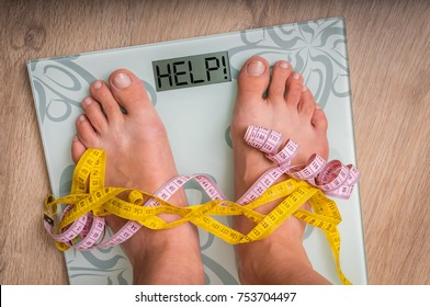 Female feet on personal scales with word HELP! - obesity and diet concept