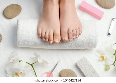 Female feet on towel roll. Nails getting a fresh and accurate look during a pedicure procedure.