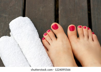 Female feet with a pink pedicure on a wooden background