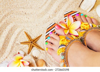 Female feet with pretty multicolor pedicure on sand, with frangipani flowers and seashells. Summertime concept, top view