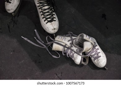 Female feet rolling on skates on the ice rink close up