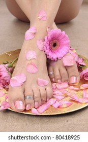 Female feet with rose petals and flowers