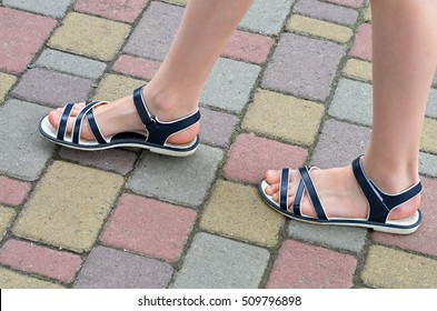 female feet in sandals are on the sidewalk
