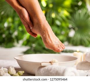 Weibliche Füße mit Meersalz auf weißem Hintergrund und tropisch-grüner Hintergrund