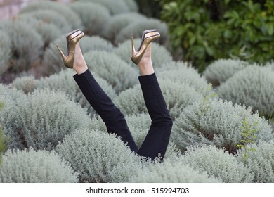 Female feet in shoes sticking out from the grass