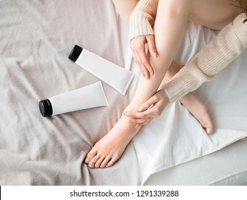 Female feet and skin care cream in tubes on the bed. Skin care concept.