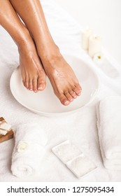 Female feet soaked in a bowl of water on white background