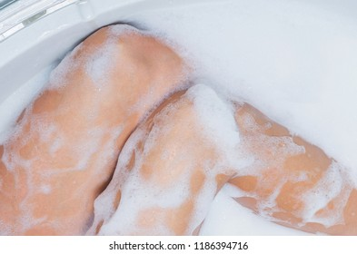Female feet in soap bath, skin care and epilation concept image. Part of body, selective focus.