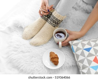 Female feet in socks with cup of tea  on fluffy blanket