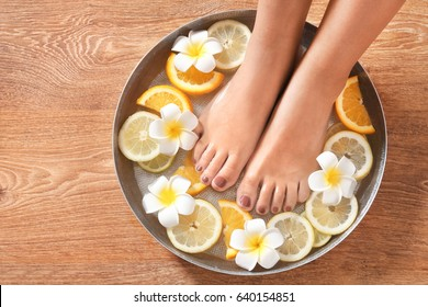 Female feet in spa bowl with citrus fruits on wooden background