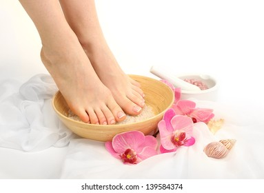 Female feet in spa bowl with sea salt, isolated on white