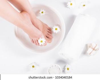 Weibliche Füße mit Spa-Schüssel, Handtuch und Blumen auf weißem Hintergrund