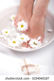 Female feet with spa bowl, towel and flowers on white background