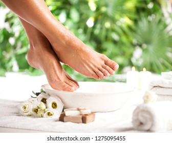 Female feet with spa bowl, towel, soap and flowers on white floor and tropical green leaves background