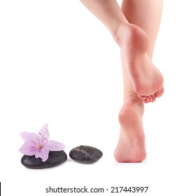 Female feet and Spa stones with spa flower isolated on white background