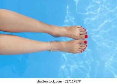 female feet  feet splashing in the swimming pool