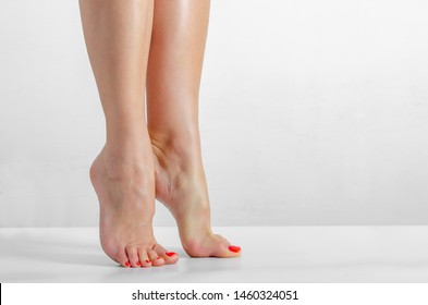 Female feet, feet stand on the fingers on a white background, Smooth skin, foot care