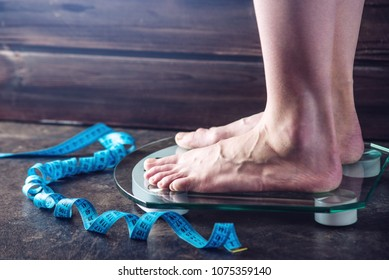 Female feet standing on electronic scales for weight control with and measuring tape on dark background. The concept of sports training, diets and weight loss