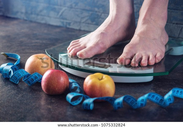 Female feet standing on electronic scales for weight control with measuring tape and apples on dark background. The concept of sports training, diets and weight loss