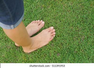 Female feet standing on green grass / Relaxing concept