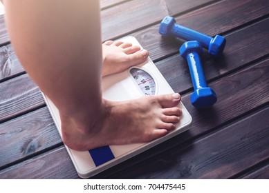 Female feet standing on mechanical scales for weight control, dumbbells and measuring tape on wooden background. The concept of sports training, slimming and weight loss