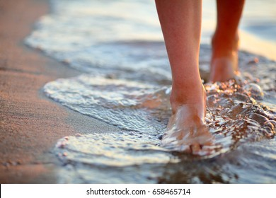 Female feet step on the sea wave. Summer vacations concept