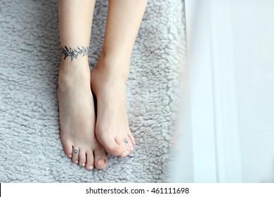 Female feet with tattoo on carpet