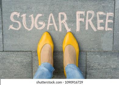Female feet with text sugar free written on grey sidewalk.