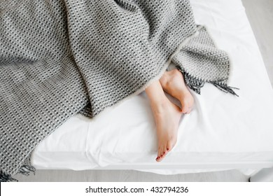 Female feet under blanket flat lay. Female beautiful feet with red pedicure on the bed. Top view on the sleeping woman legs under gray blanket