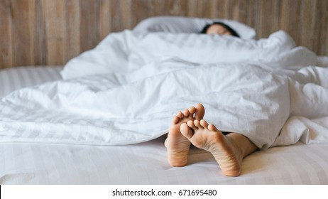 Female feet under blanket flat lay. Female beautiful feet on the bed. Sleeping woman legs under white blanket