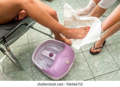 Female feet in a vibrating foot massager. Electric massage foot bath. Relax after work.