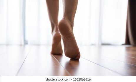 Female feet walking on warm heated floor close up view, barefoot girl legs going on hardwood living room wooden flooring at modern home house, domestic underfloor heating concept, close up rear view