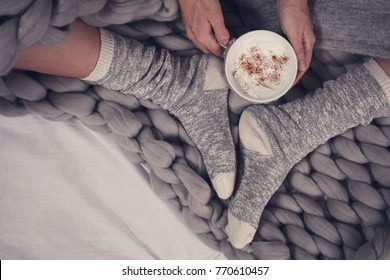 Female feet wearing cozy warm wool socks close up. Woman covered with warm blanket drinking coffee in bed .