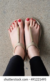 Female feet wearing slippers or flip-flop outdoor red nail great for any use.