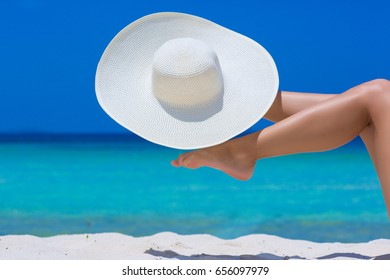 Female feet with white hat on the beach, blue sea and sky background
